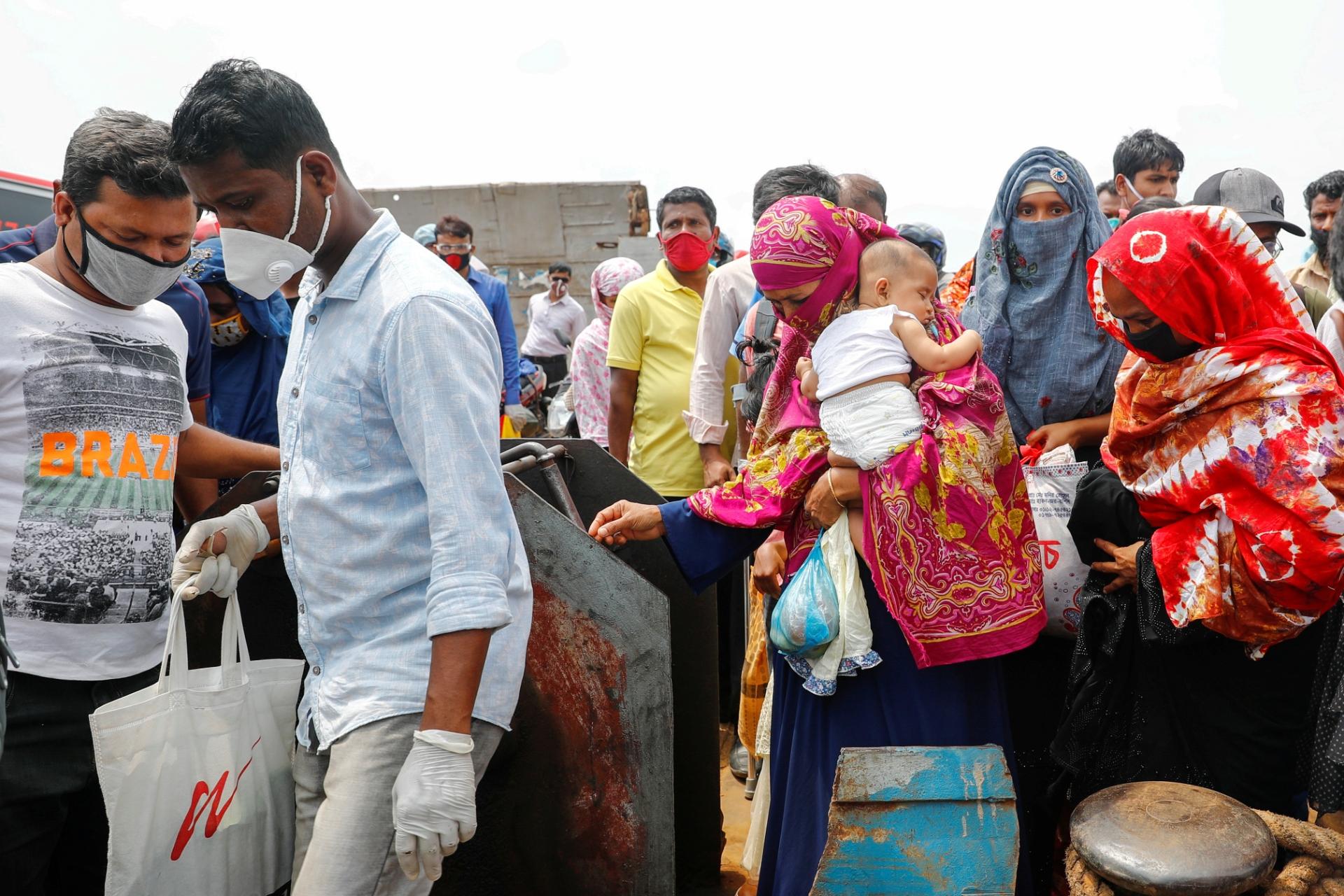 Trabalhadores migraTrabalhadores migntes chegam a Mawa Ferry Ghat, em Bangladesh