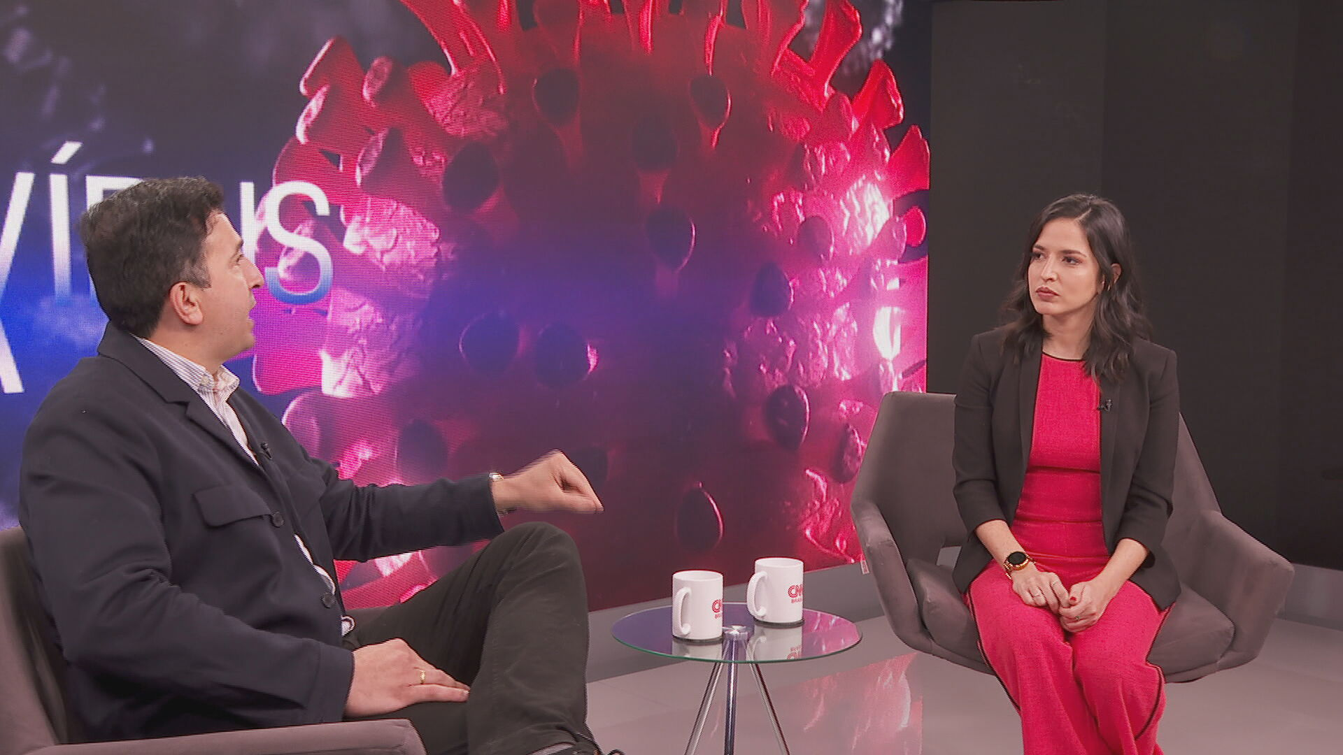 Dr. Gustavo Cabral e Karla Chaves conversam em frente à fundo com coronavírus