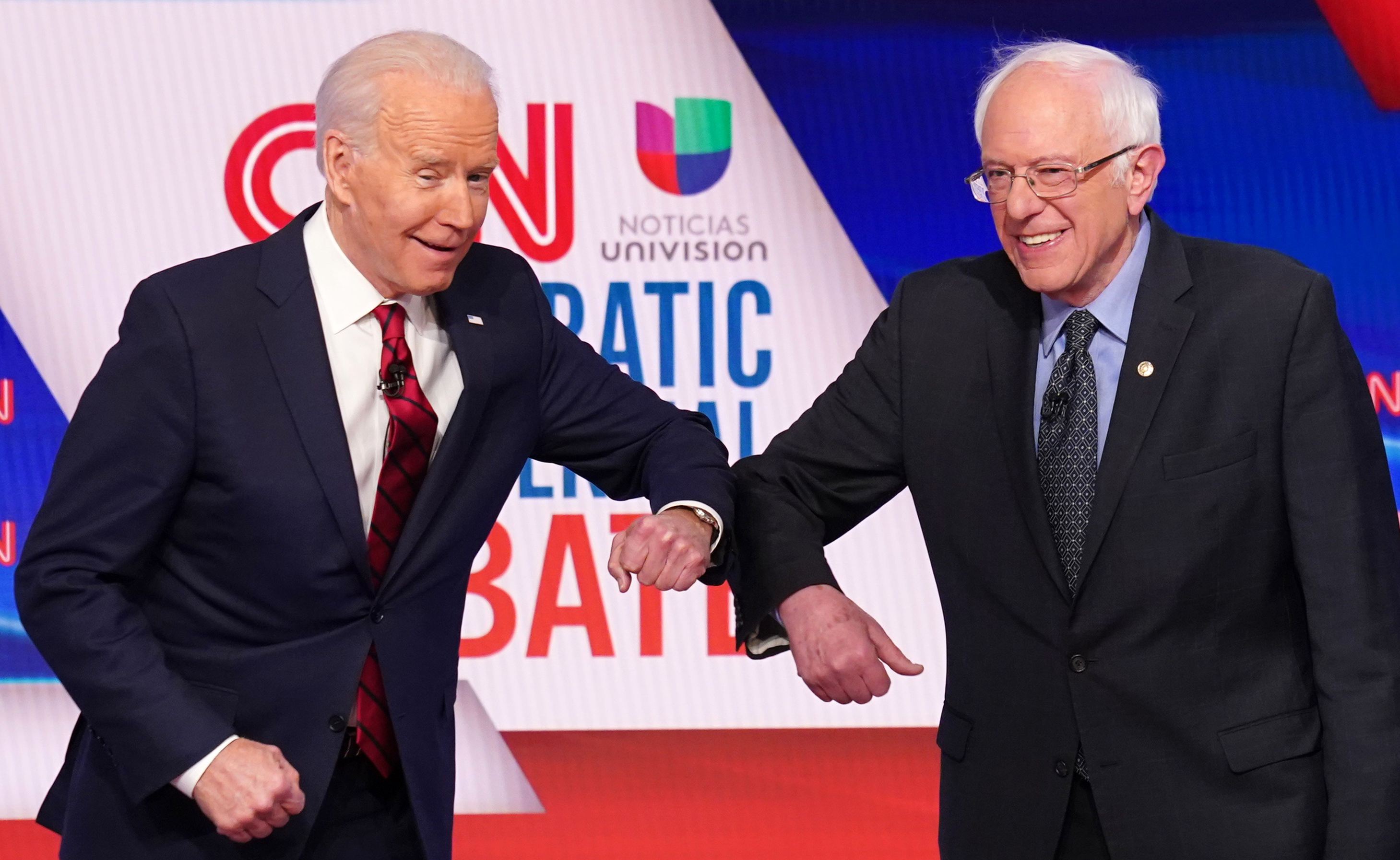 Joe Biden e Bernie Sanders se cumprimentam usando os cotovelos