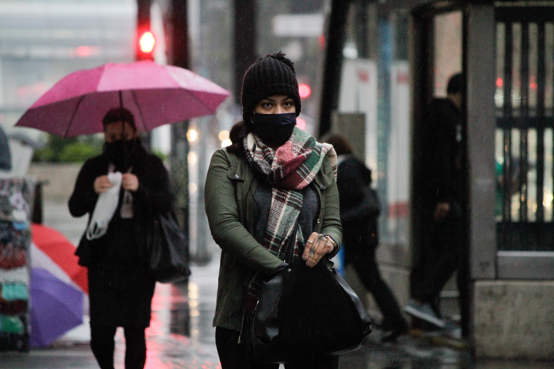 Pedestres se protegem do frio e da chuva na Avenida Paulista, em SP