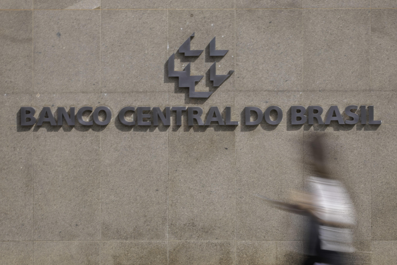 Pessoa caminha em frente a letreiro do Banco Central