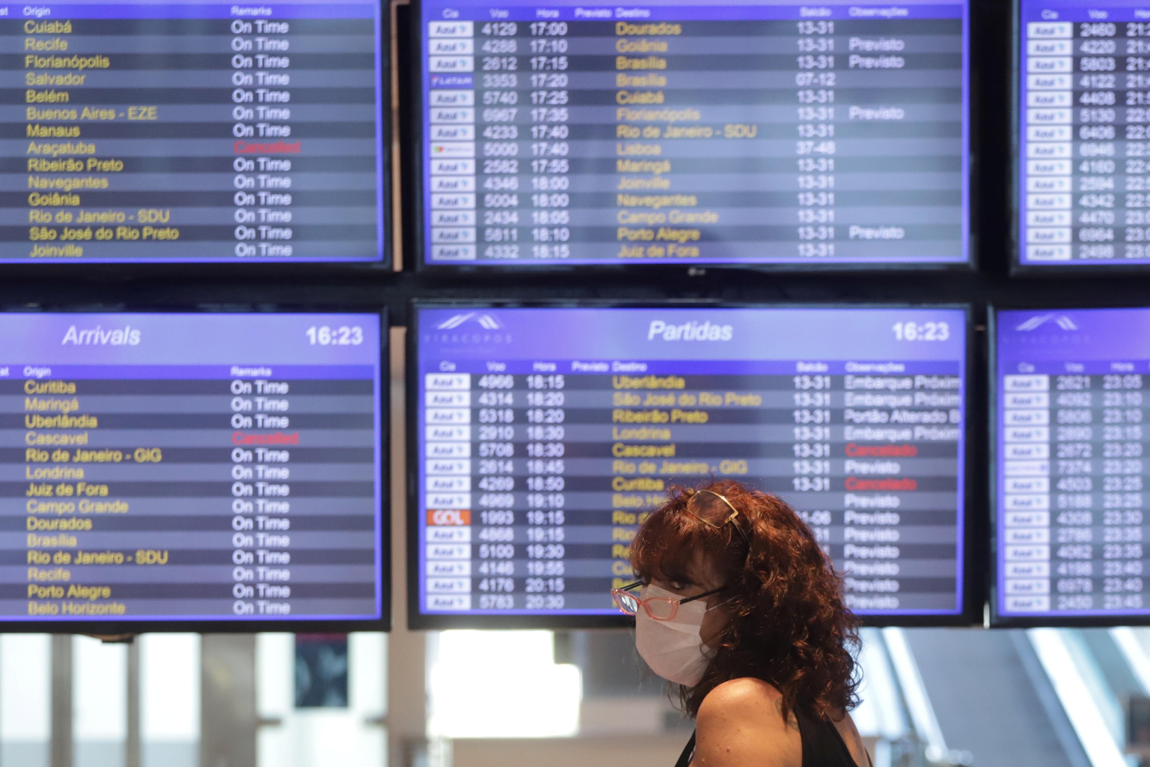 mulher usa máscara em aeroporto