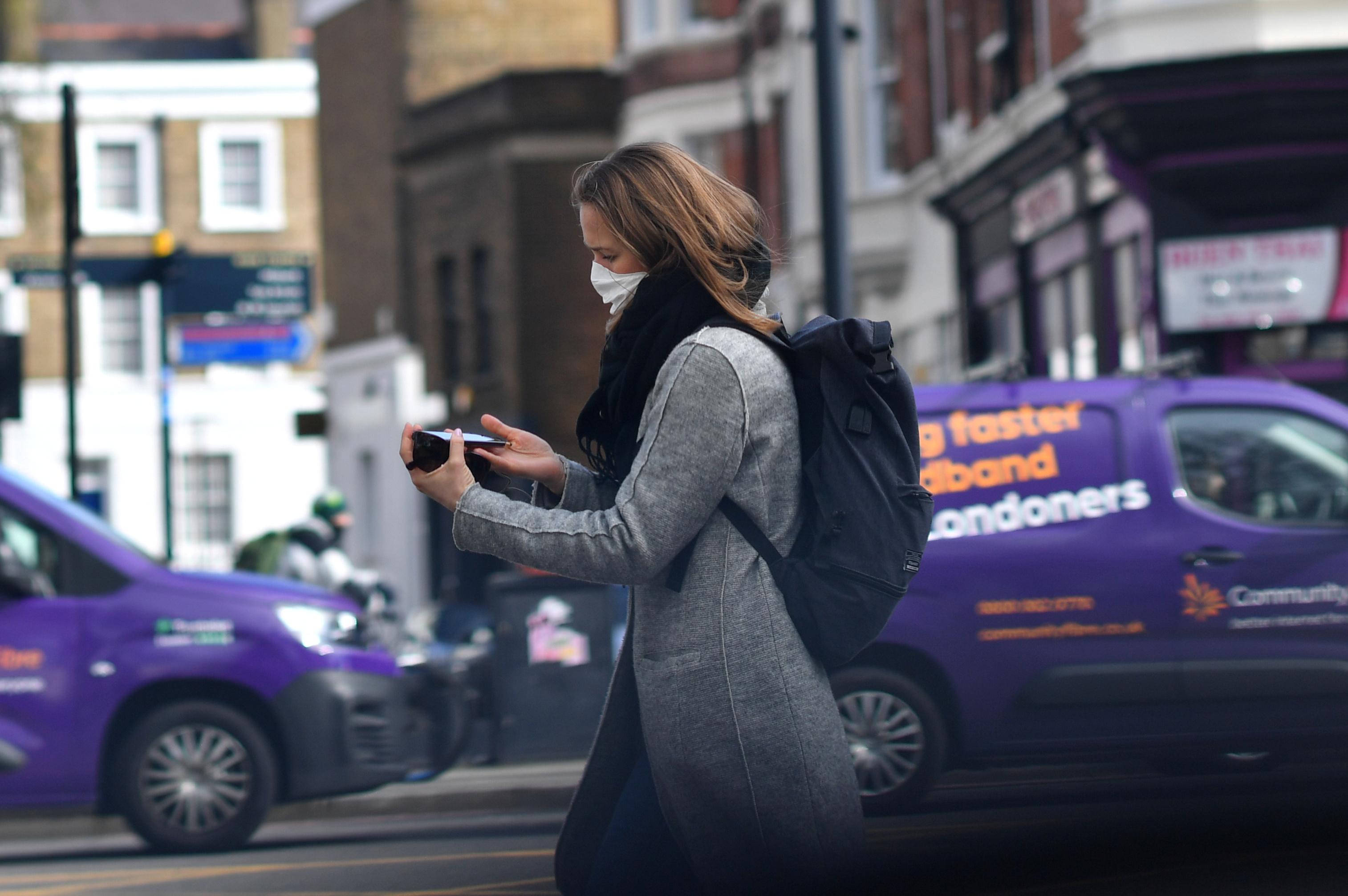 Mulher usa máscara enquanto caminha por Londres de olho no celular