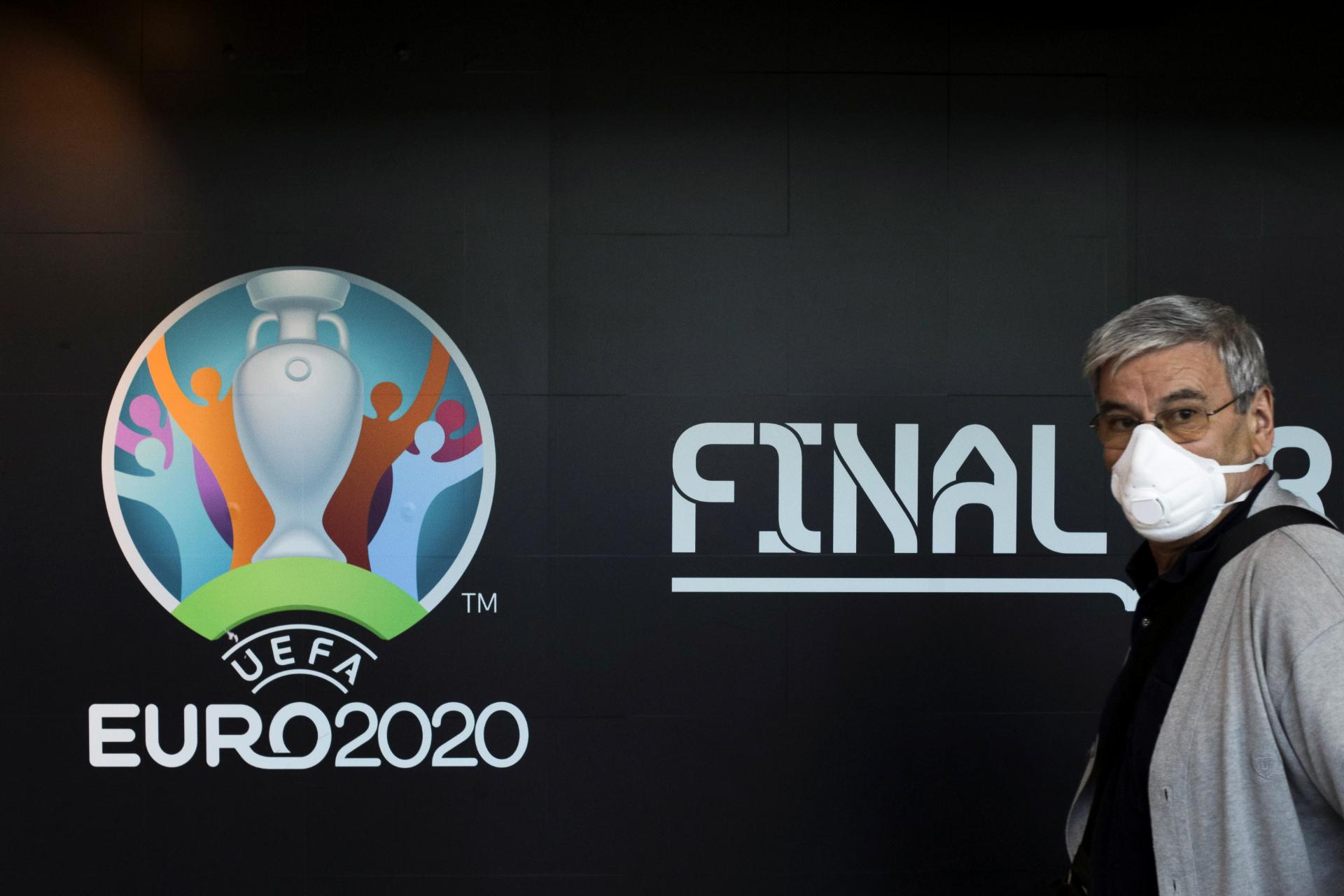 Homem com máscara de proteção passa pelo logo da Euro 2020