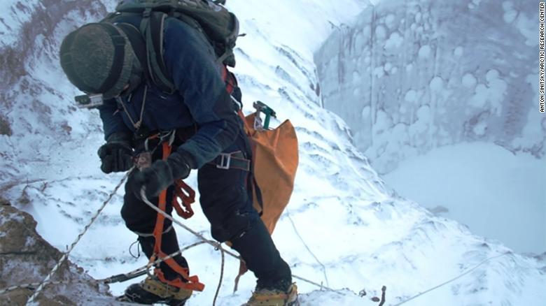 Alpinista descendo a cratera na tundra siberiana