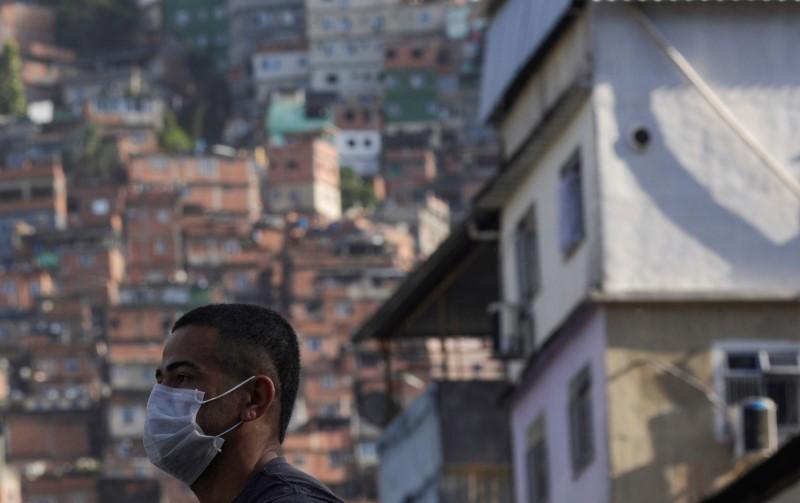 Homem espera ônibus na favela da Rocinha, no Rio de Janeiro