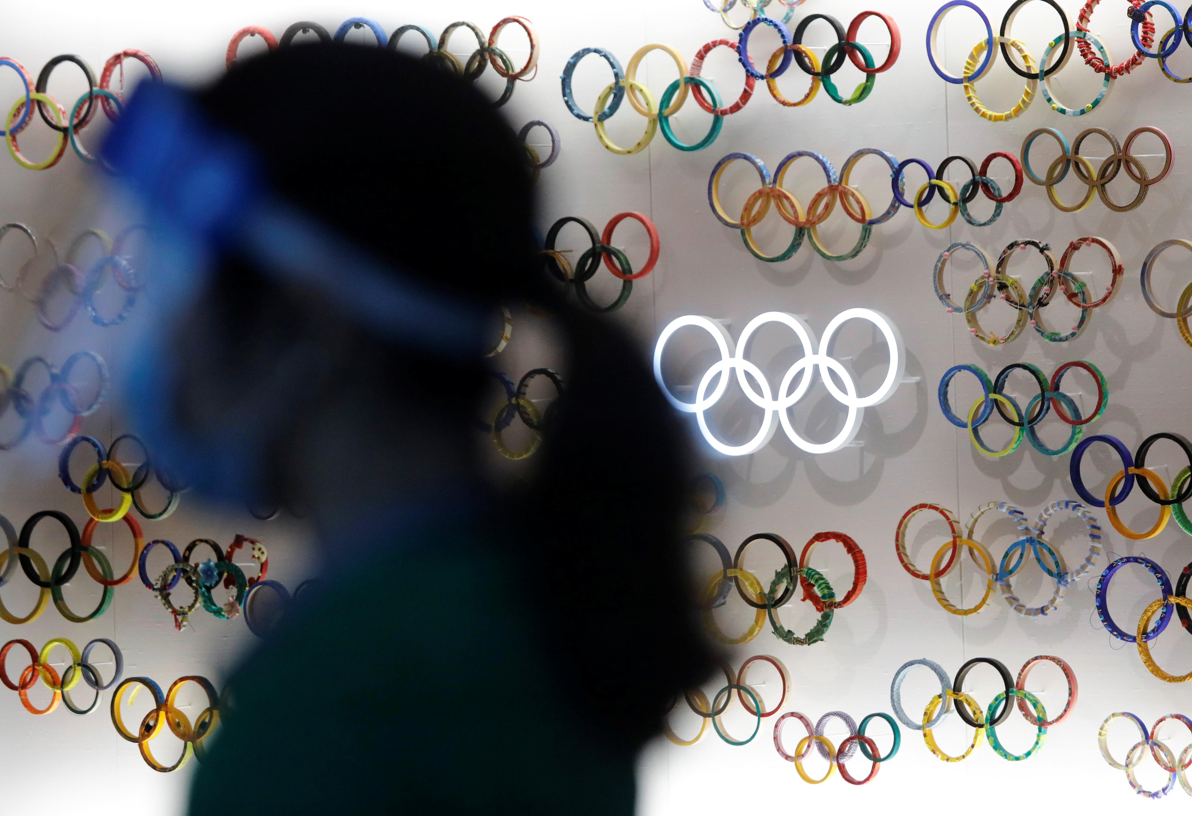 Pessoa com máscara e face shield em frente à símbolos das Olimpíadas, em Tóquio