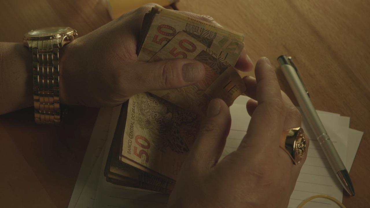 Mão segurando muitas notas de dinheiro