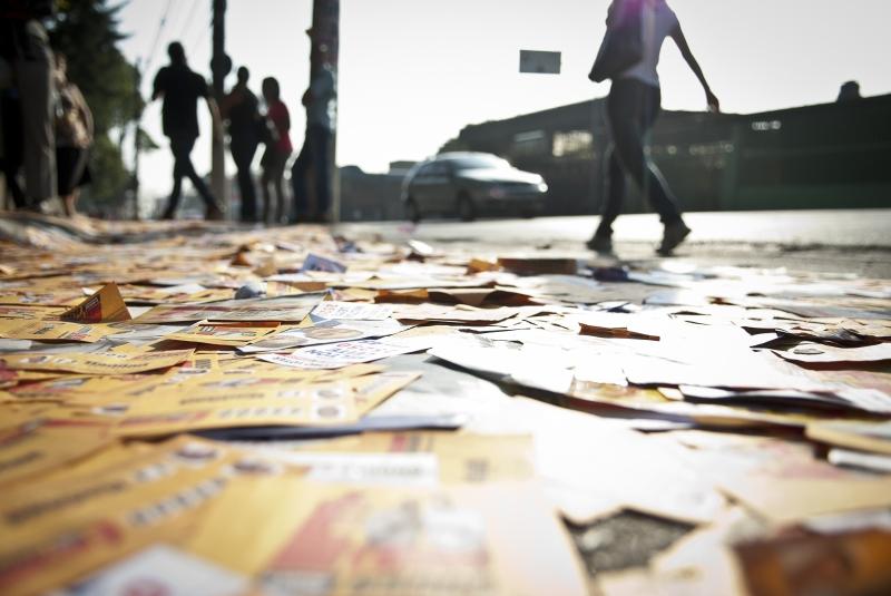 Santinhos eleitorais no chão perto de local de votação em São Paulo