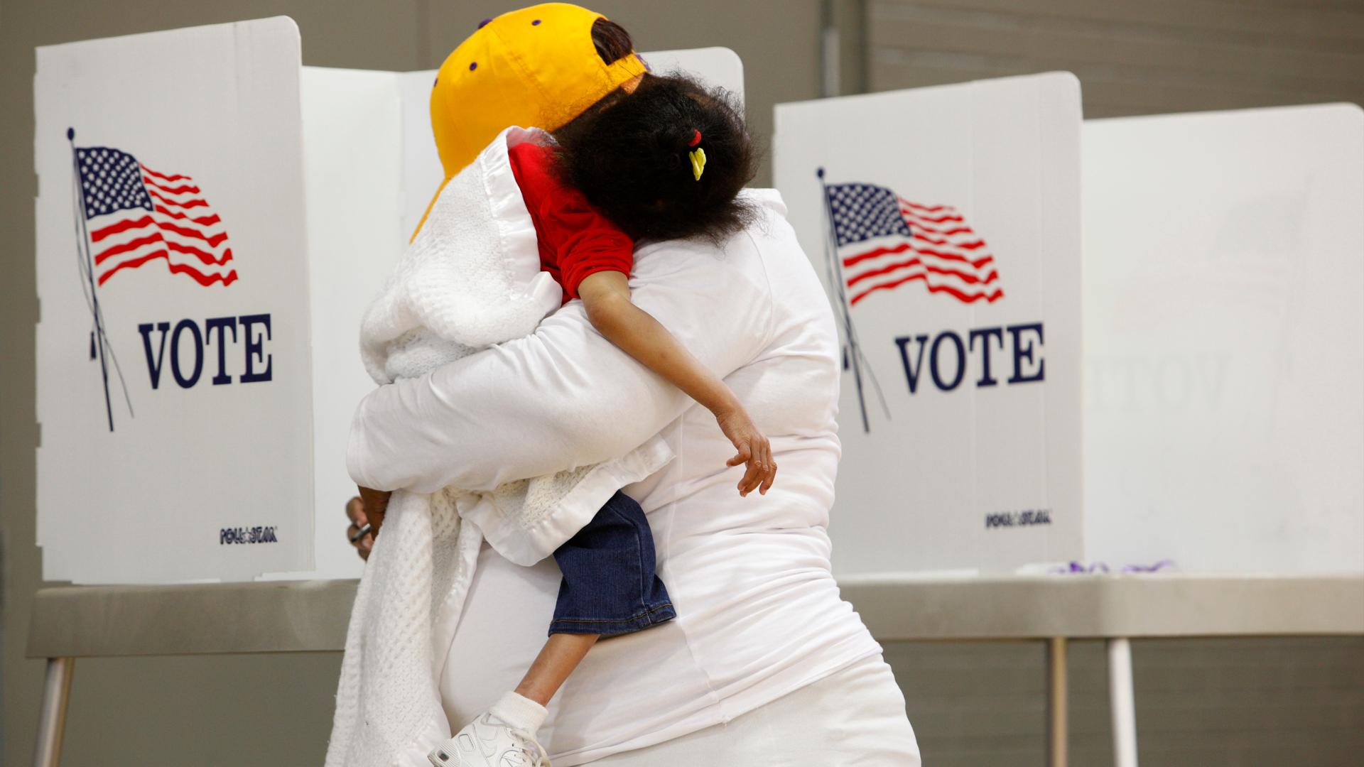 Com a filha no colo, mulher vota na eleição presidencial dos EUA, em 2016