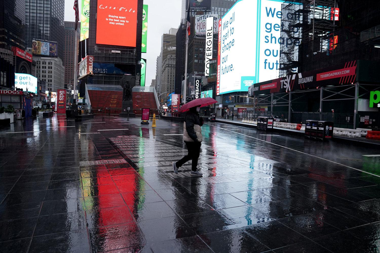 Pedestre caminha na Times Square praticamente vazia