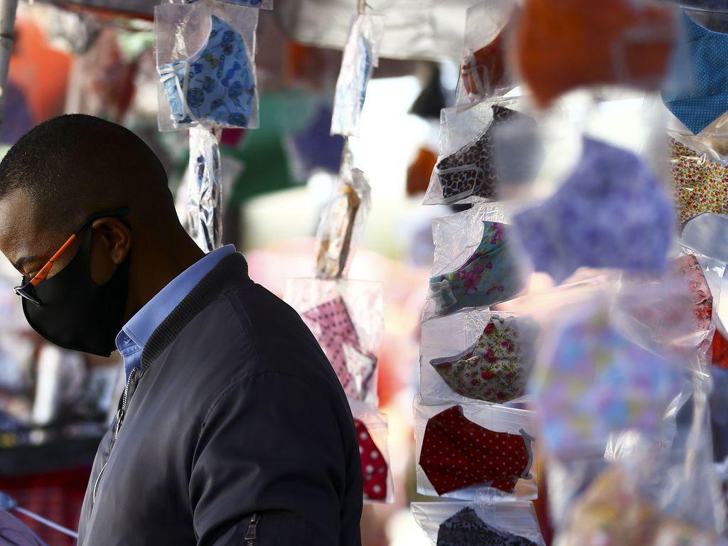 Homem de máscara em comércio de rua