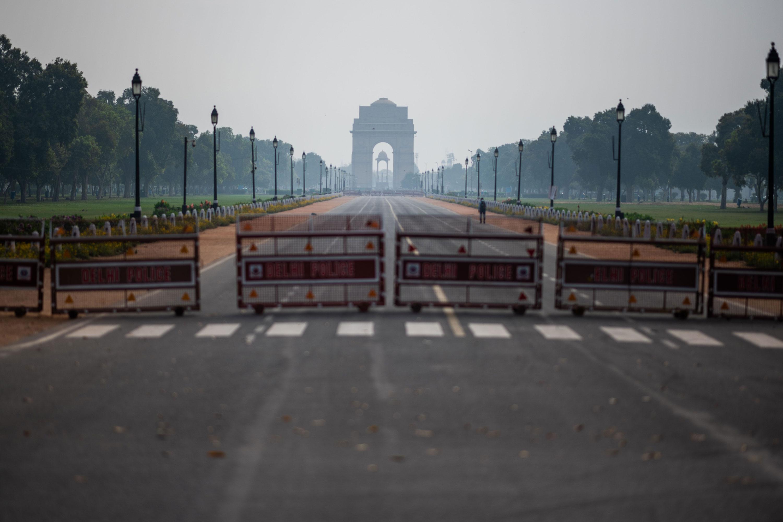 Homem caminha por rua deserta em Nova Déli em meio à pandemia do novo coronavíru