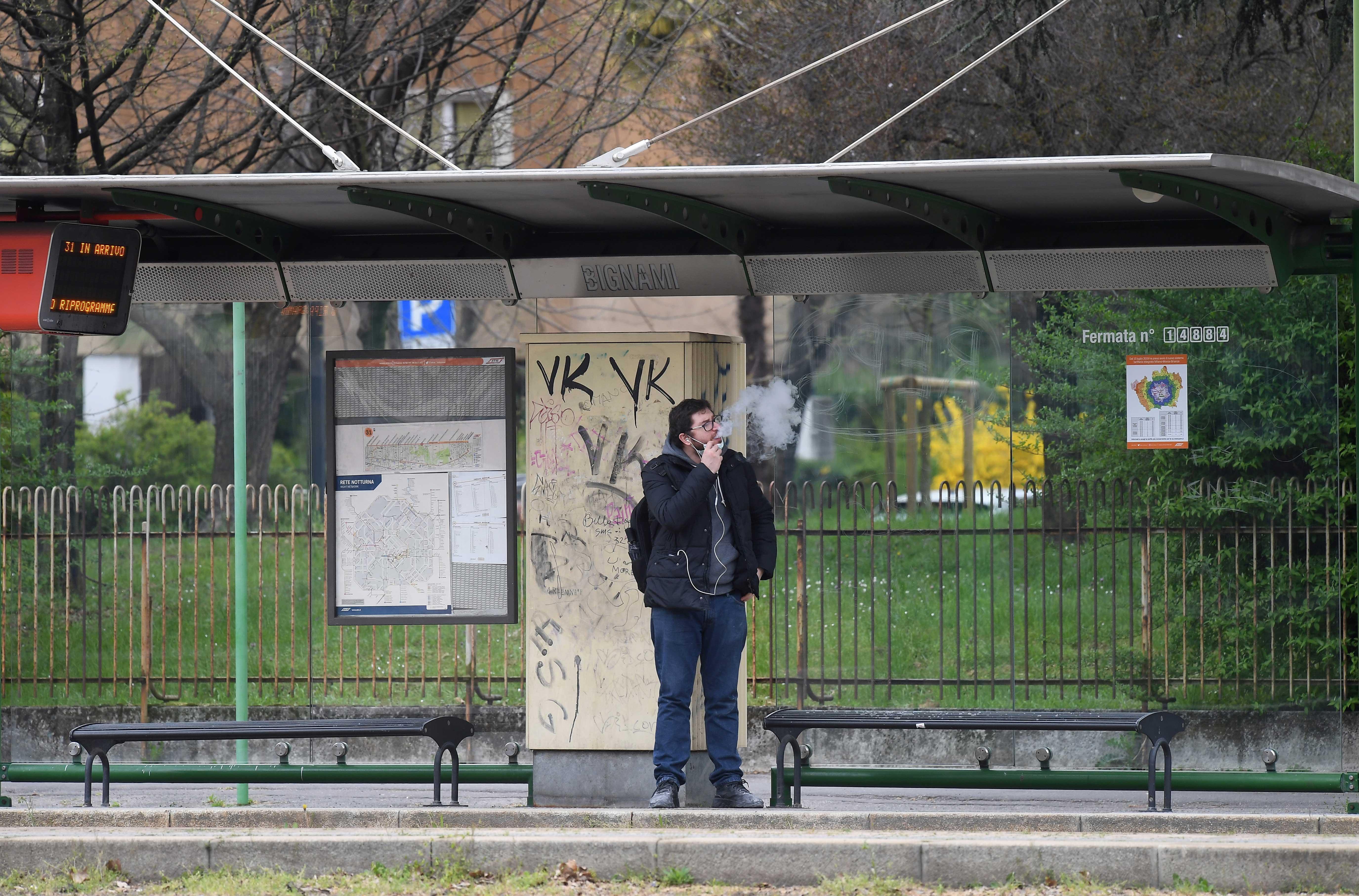 Homem fuma em ponto de ônibus em Milão, Itália