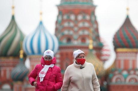 Mulheres de máscara na Praça Vermelha em Moscou