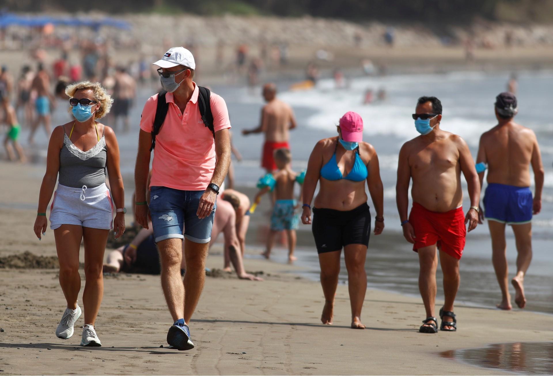 Pessoas caminham de máscara em praia das Ilhas Canárias