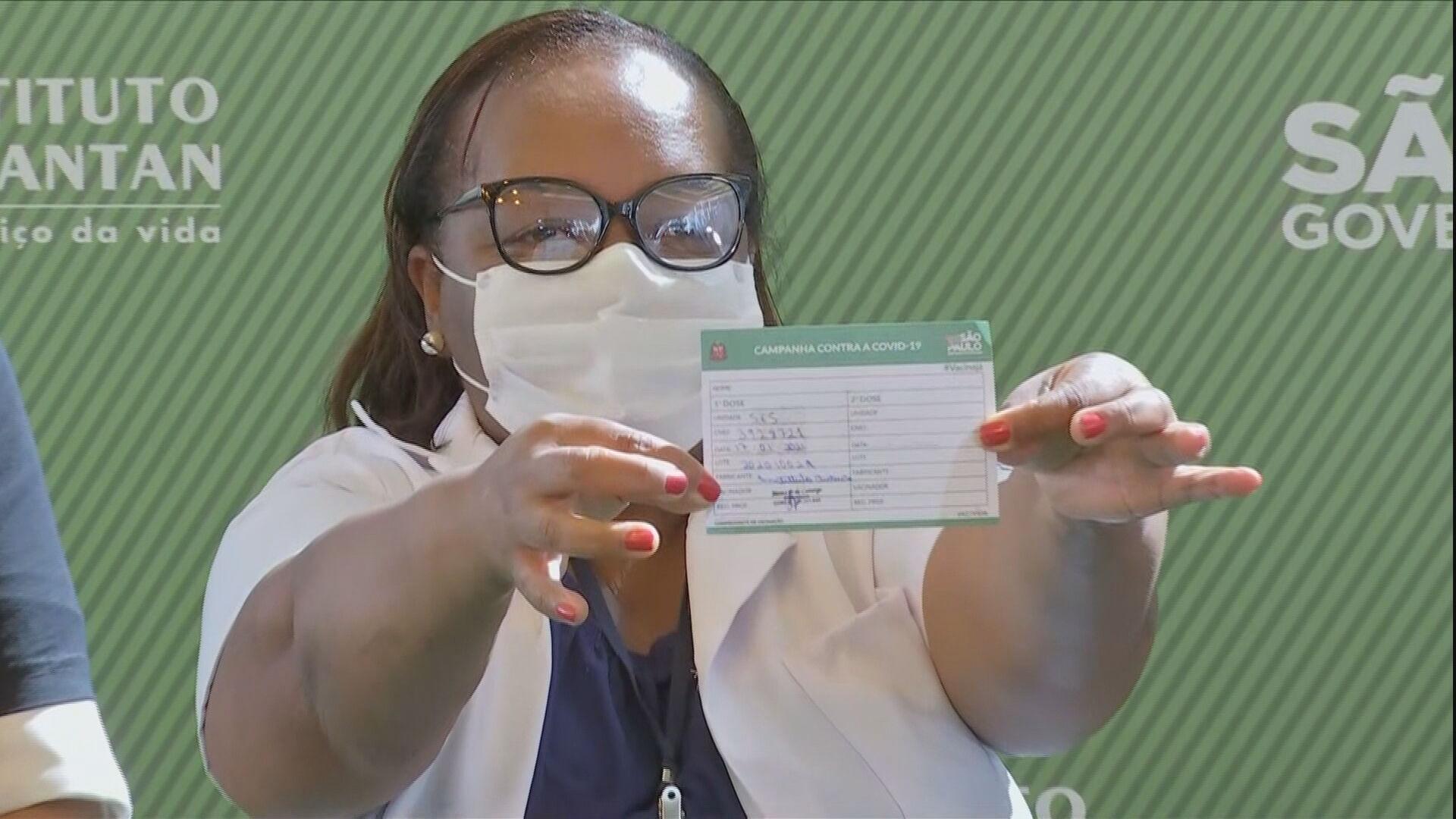 Primeira brasileira vacinada no Brasil exibe seu cartão de vacinação