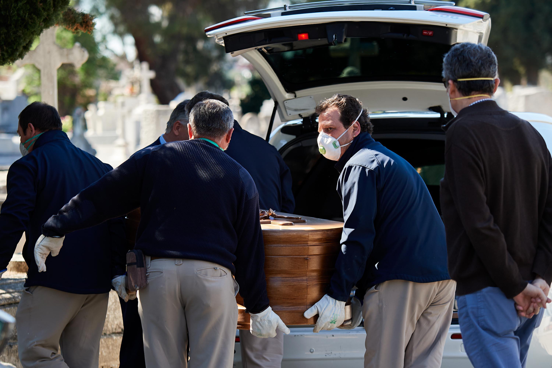 Funcionários do cemitério em Madri e parentes de vítima de COVID-19 tiram caixão