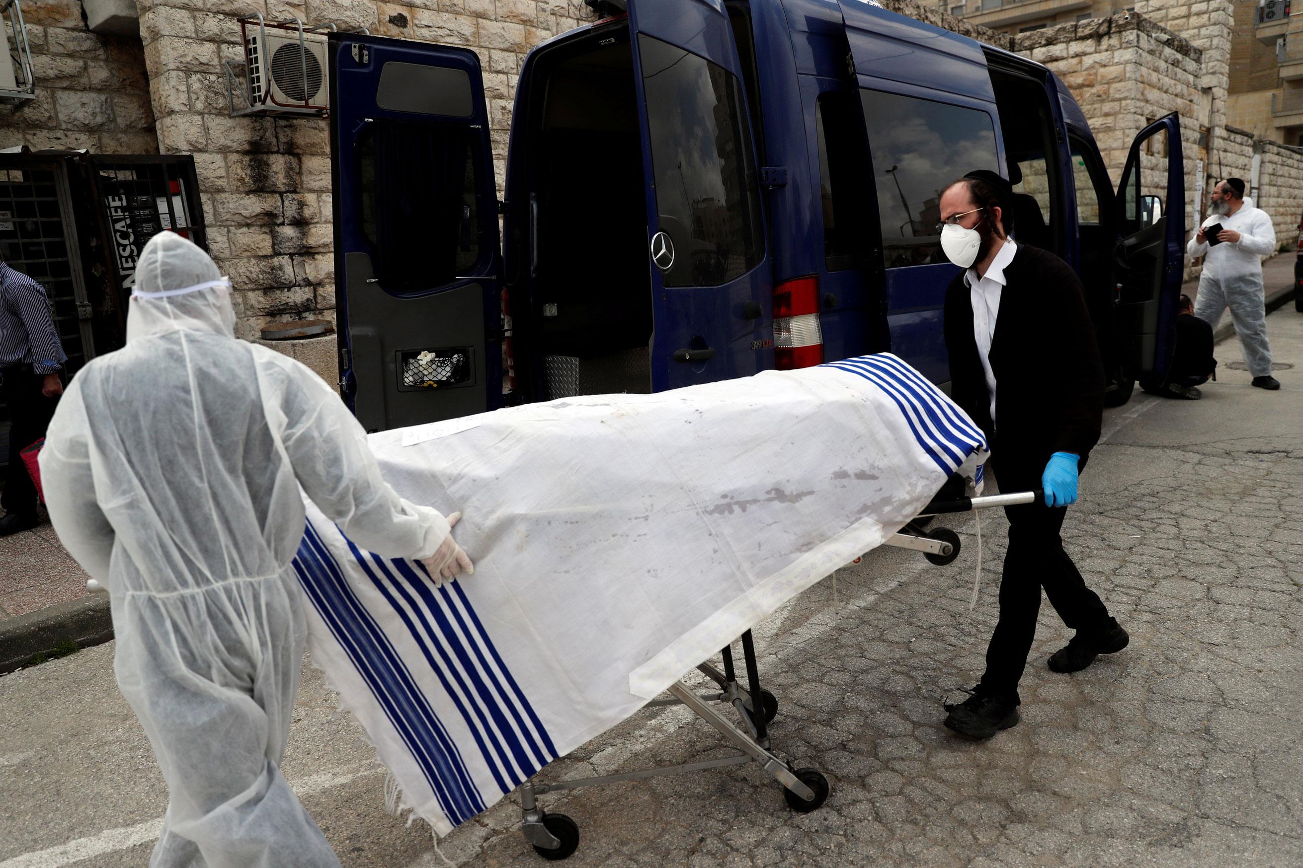 Agentes funerários transferem corpo de vítima do coronavírus em Israel