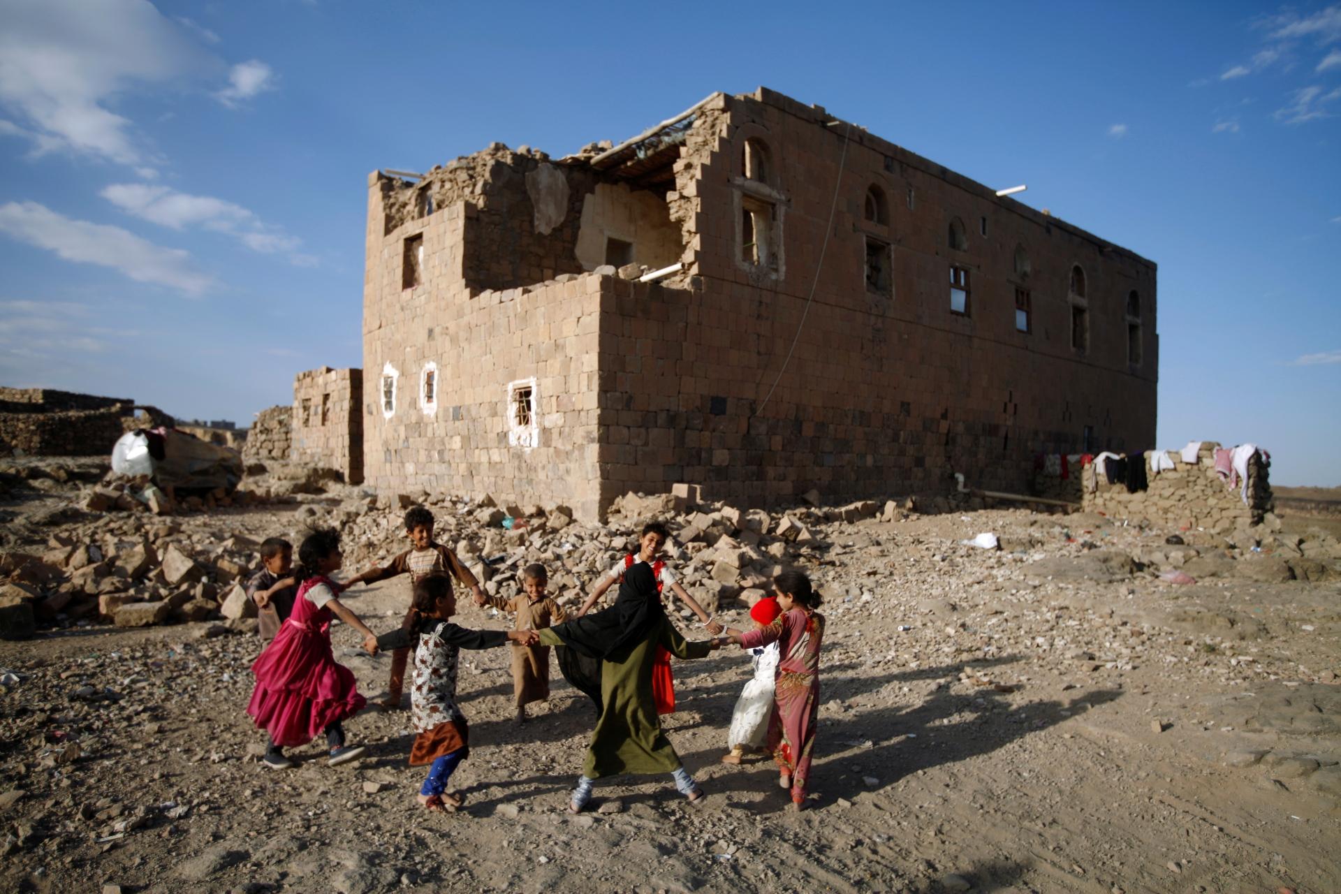 Crianças brincam perto de casa destruída por ataque aéreo nos arredores de Sanaa