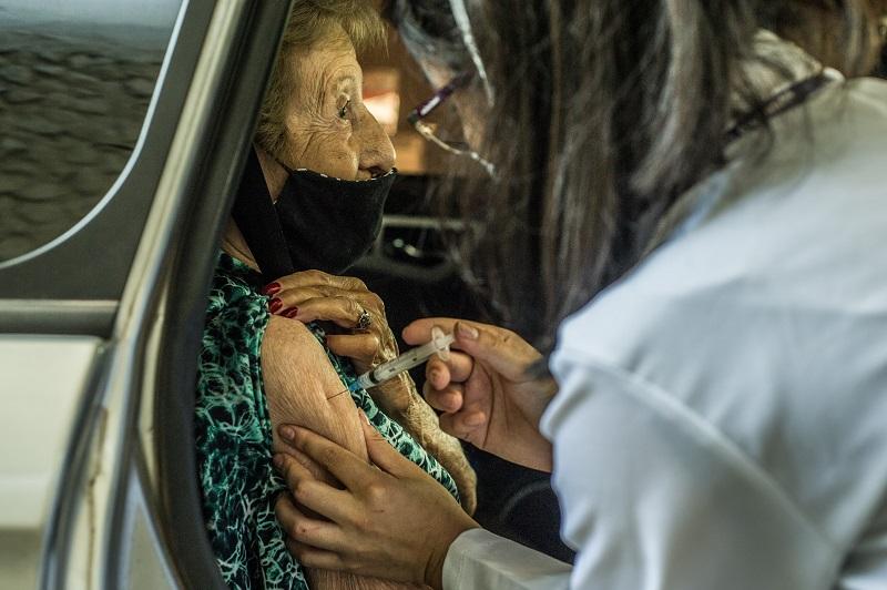 Idosa é vacinada contra o coronavírus em sistema drive-thru