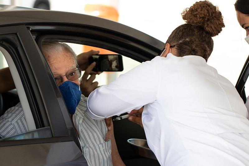 Profissional de saúde aplica vacina em idoso no Rio de Janeiro