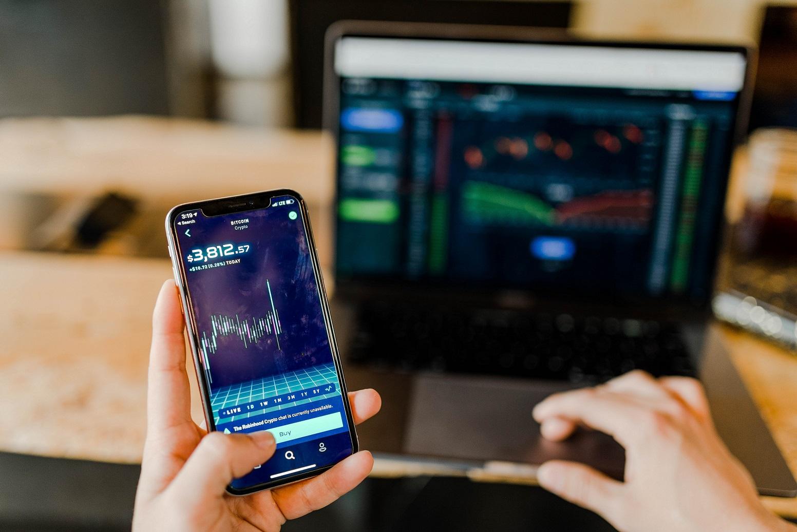 Pessoa segura celular e acompanha investimentos