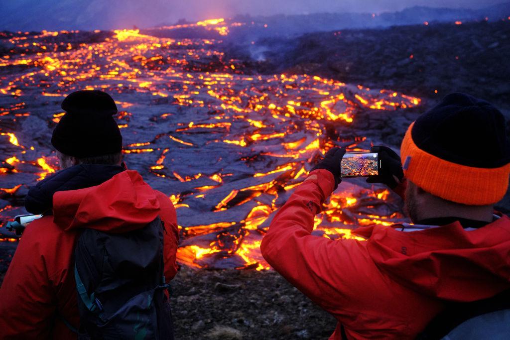 Turistas tiram foto perto da crosta de magma de vulcão na Islândia