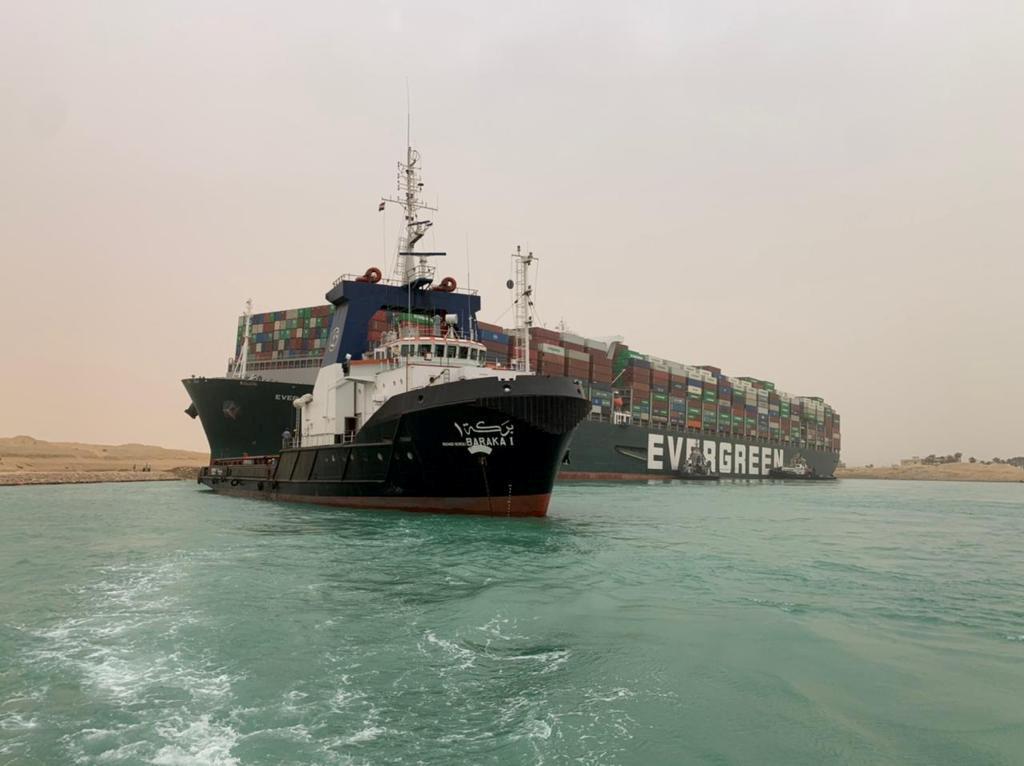 Rebocador trabalha para tentar desencalhar porta-contêineres no Canal de Suez