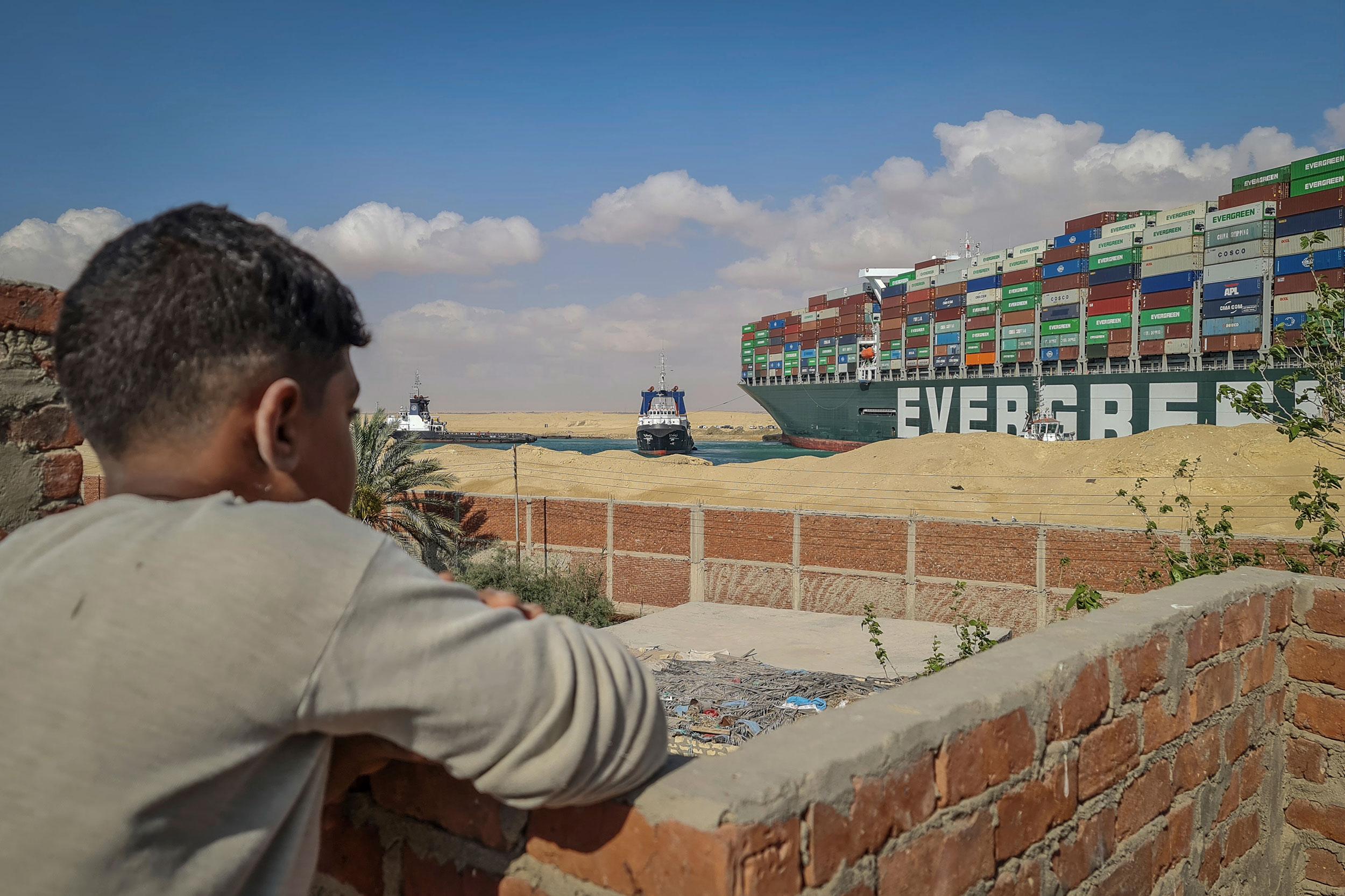Garoto observa rebocadores tentarem desencalhar navio no canal de Suez