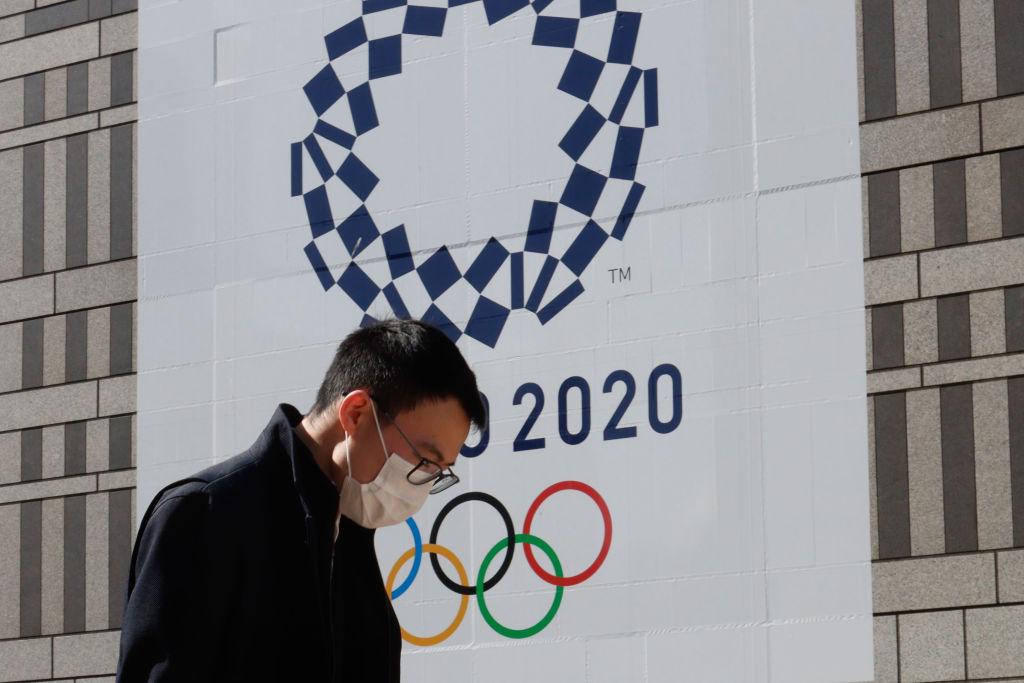 Homem de máscara passa em frente ao símbolo da Olimpíada de Tóquio