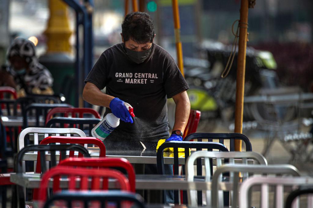 Funcionário higieniza mesas para reabertura de restaurantes