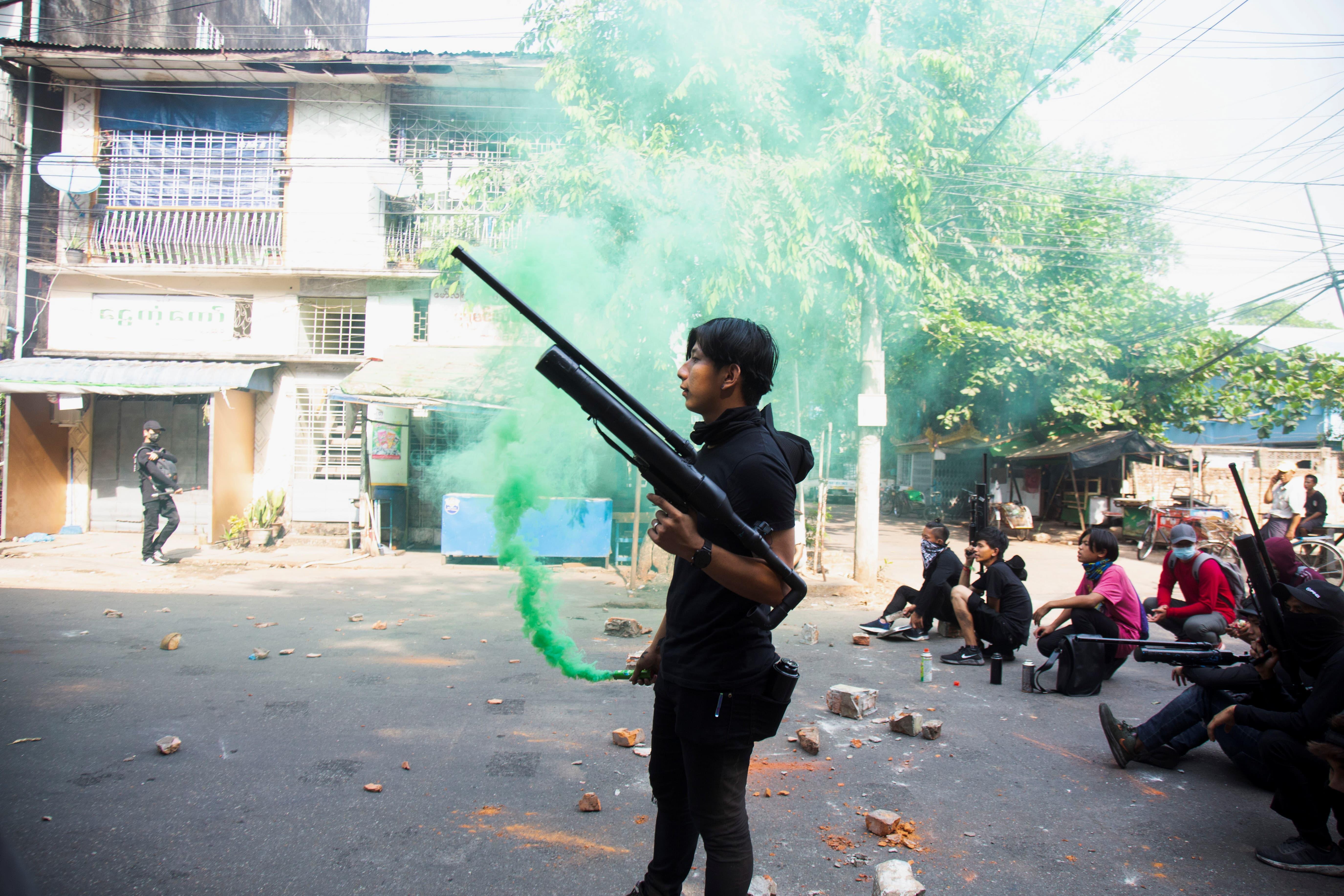 Manifestante segura arma feita com canos durante protesto em Mianmar