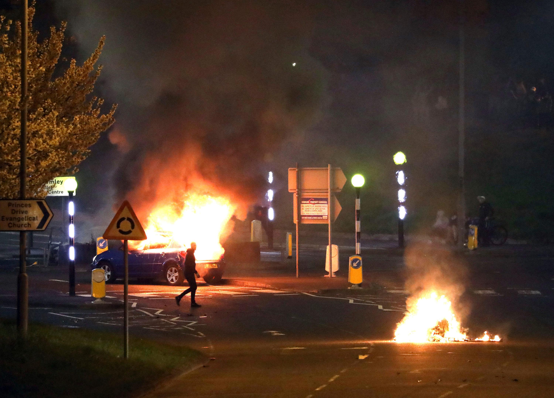 Homem caminha na frente de carro pegando fogo em Belfast, no norte da Irlanda