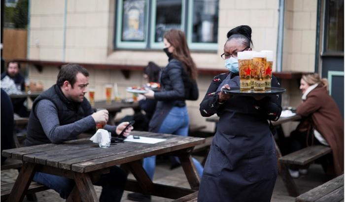 Garçonete serve clientes em pub da Inglaterra