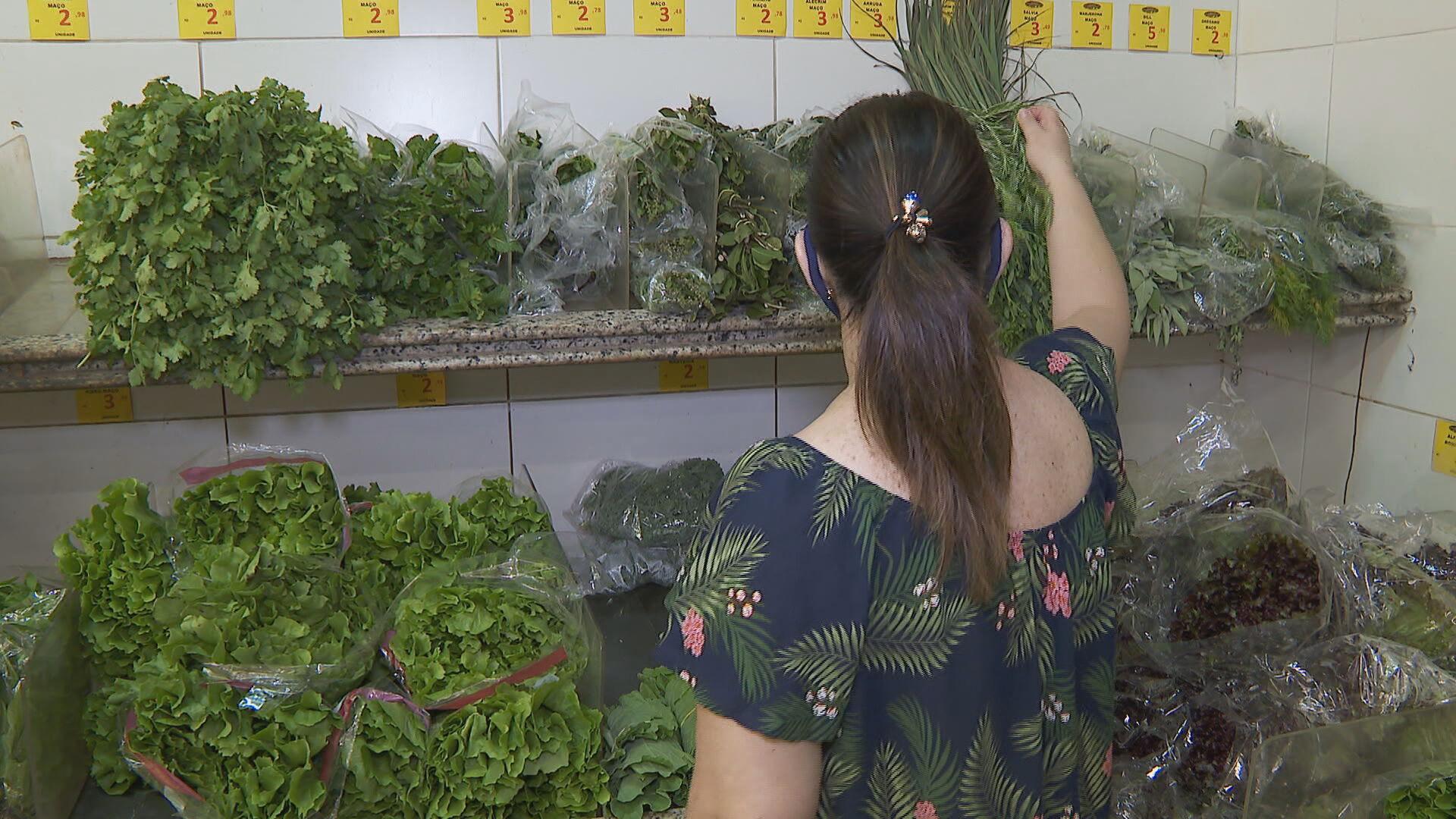 Consumidora escolhe verduras em mercado (18 de abril de 2021)