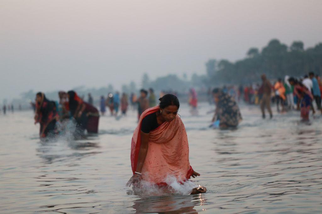 Mulher celebra rito hindu na Baía de Bengala