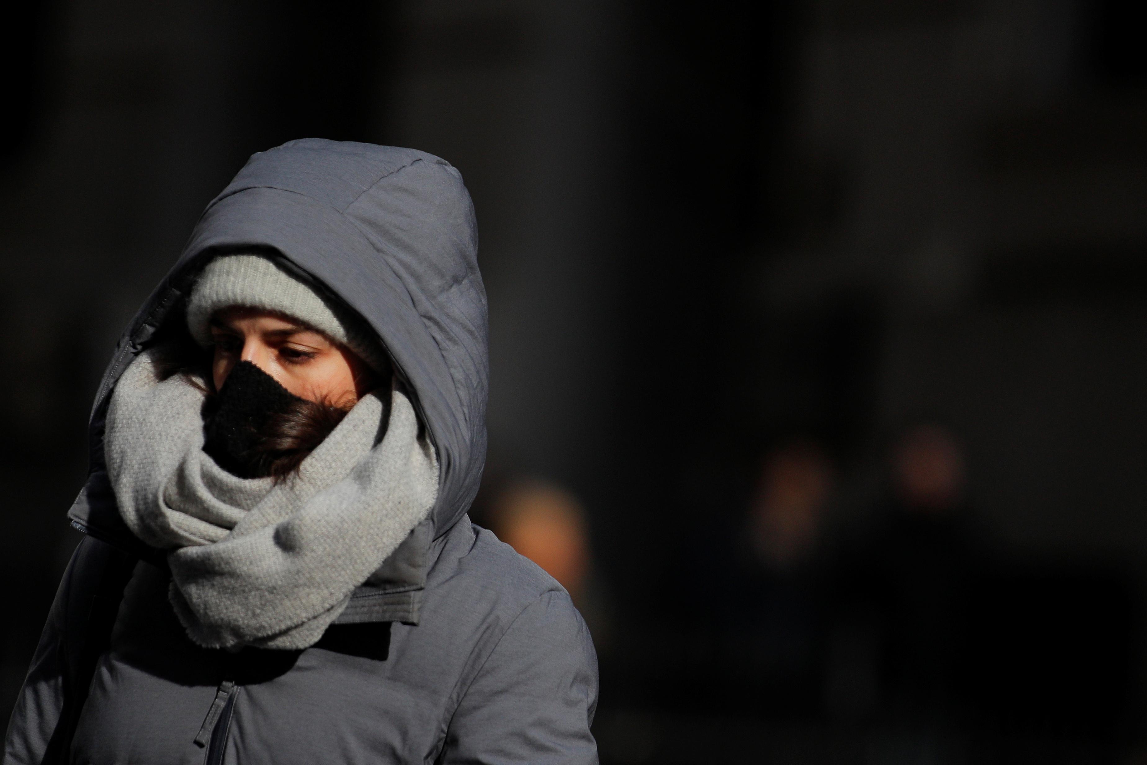 Mulher caminha de máscara em rua de Nova York