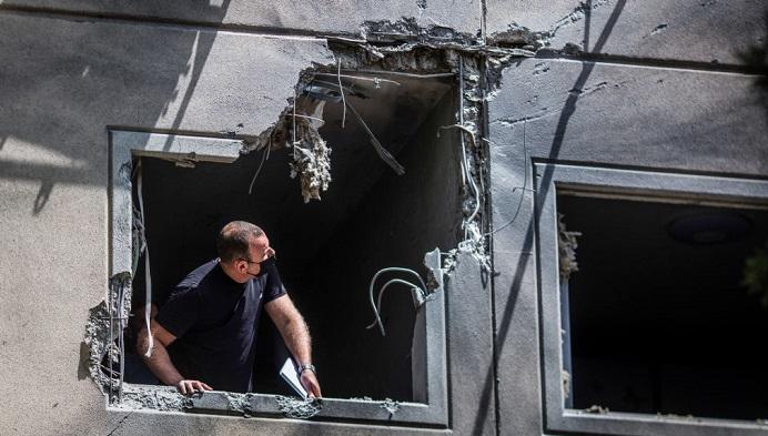 Um homem inspeciona uma janela destruída em uma casa atingida por um foguete