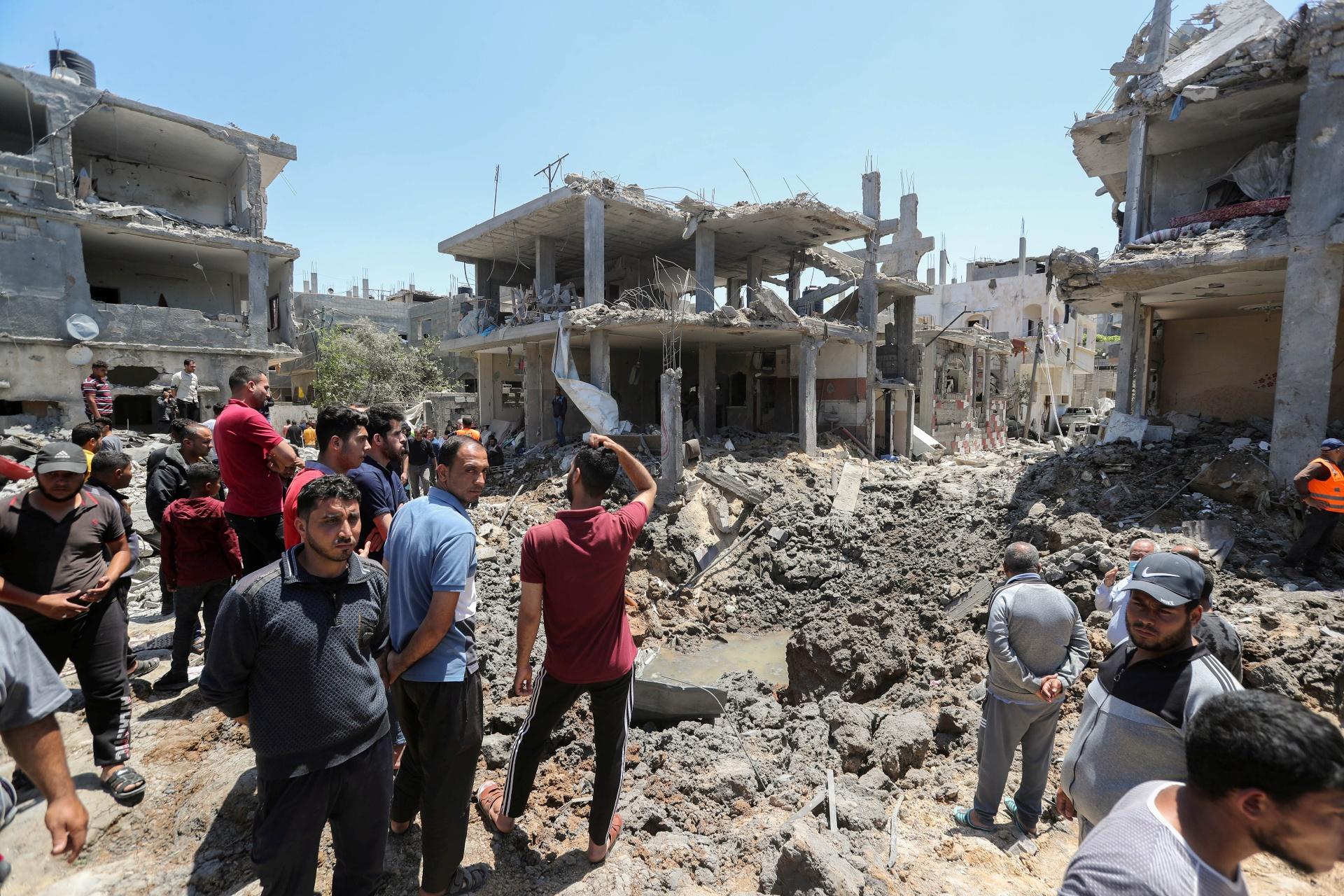 Palestinos se reúnem perto de casas destruídas por ataque de Israel em Gaza