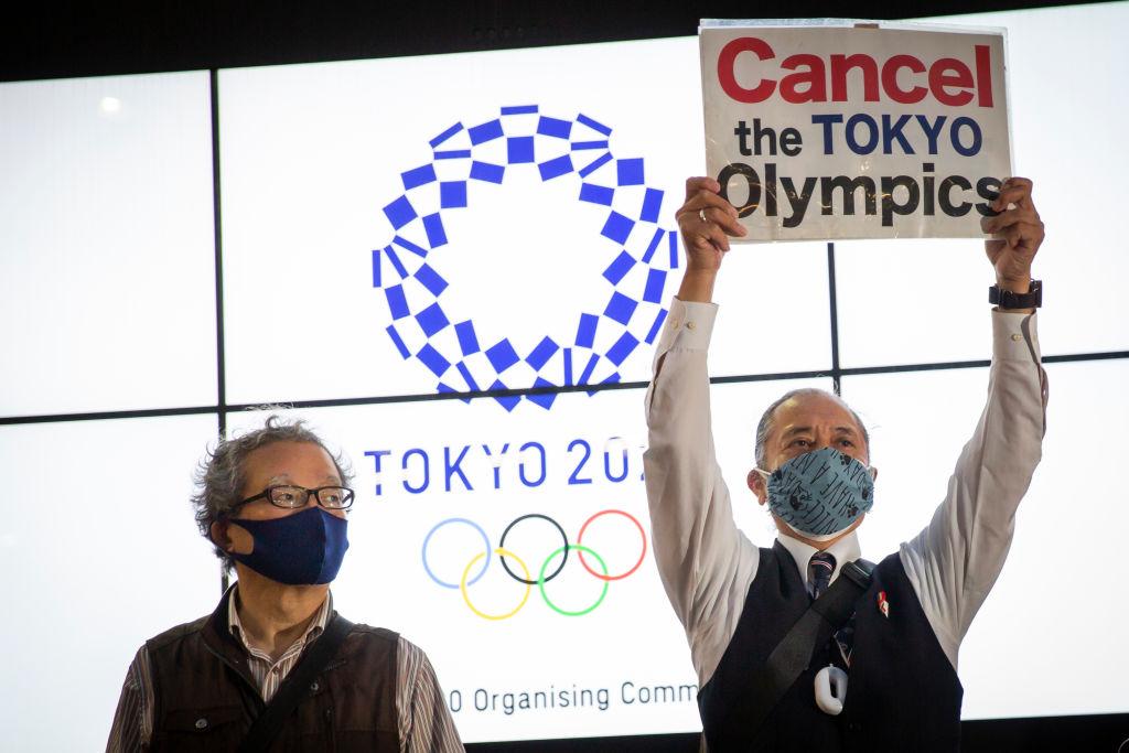 """Manifestante segura cartaz que diz """"Cancelem a Olimpíada de Tóquio"""""""