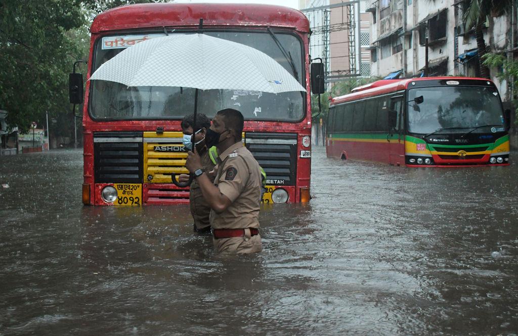 Policiais em ruas alagadas de Mumbai