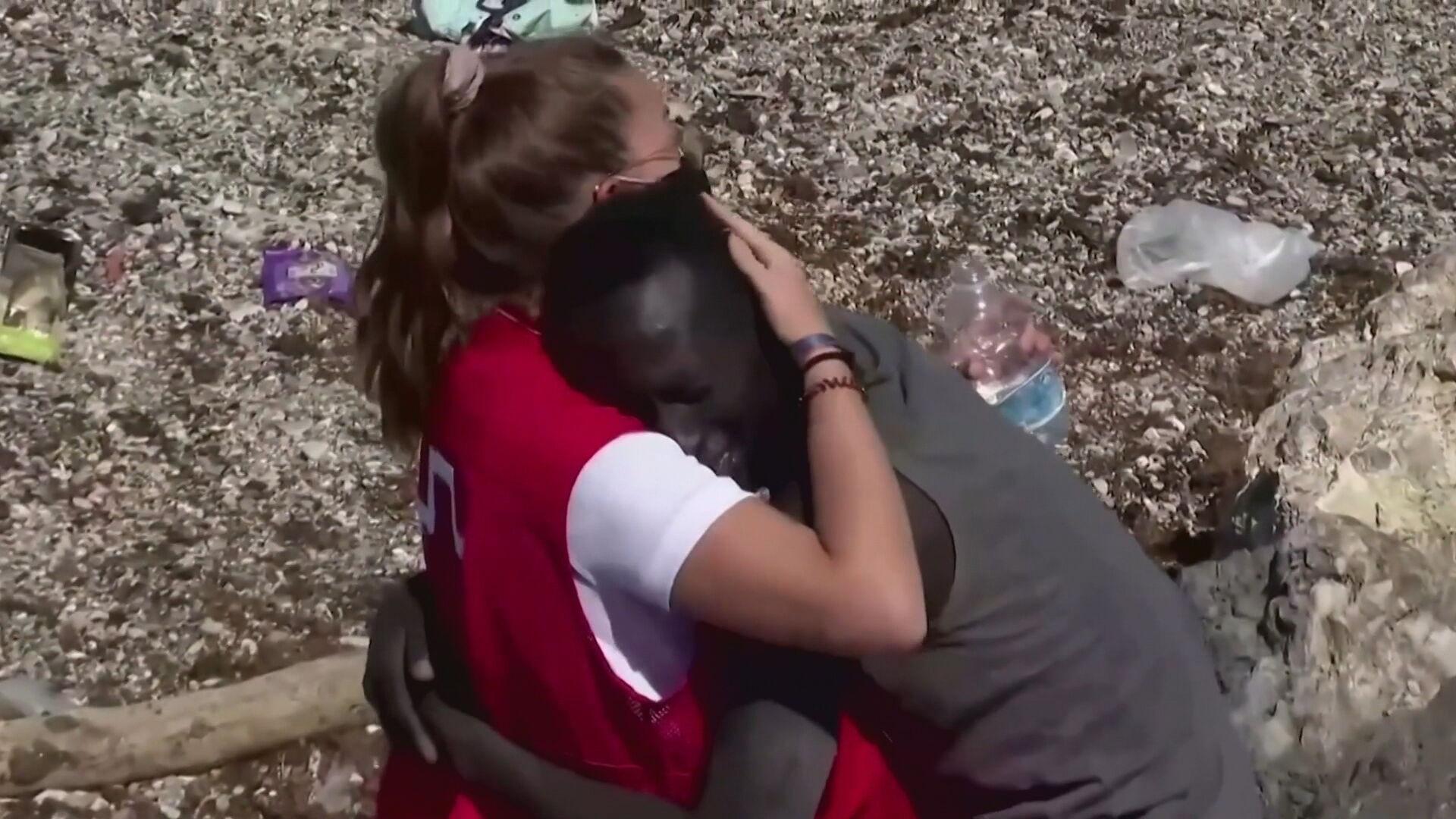 Voluntária da Cruz Vermelha abraça um imigrante senegalês em Ceuta