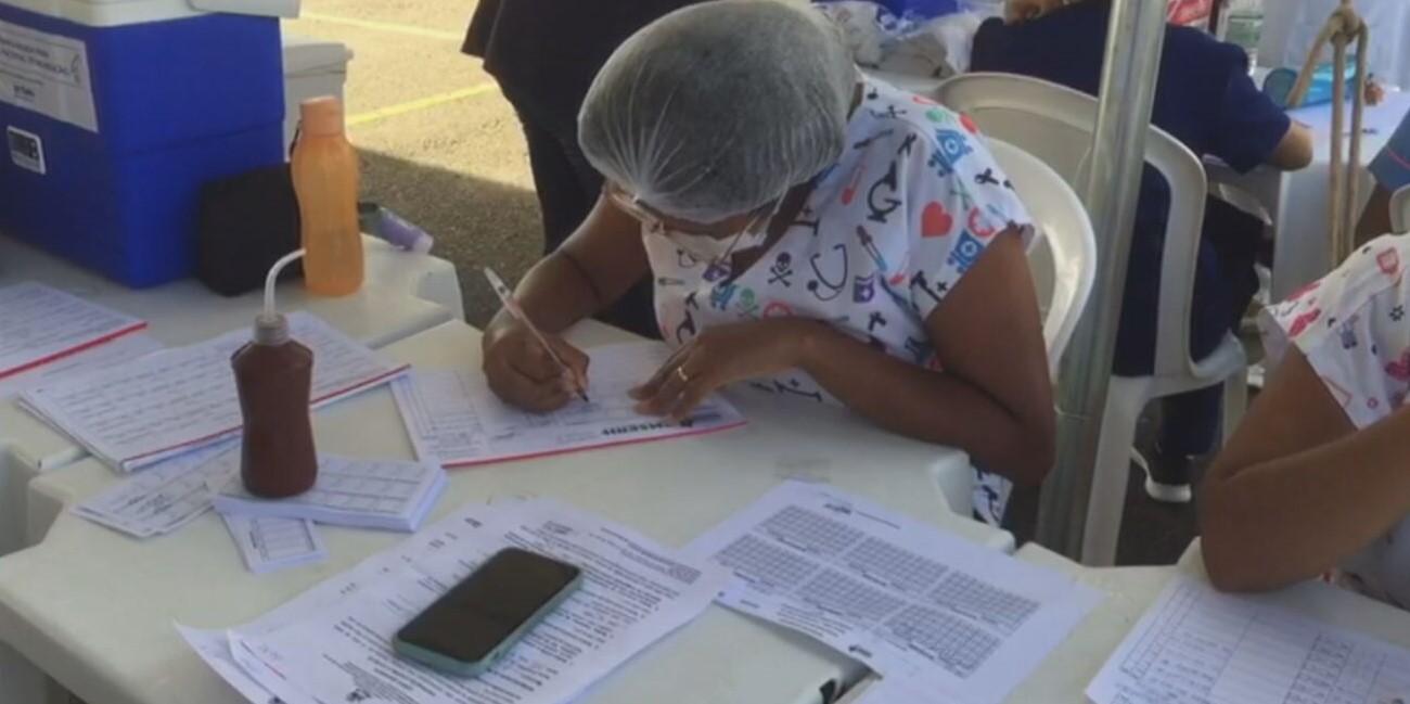 Agente de saúde realiza cadastramento de vacinados ao longo do 'Arraiá da Vacina