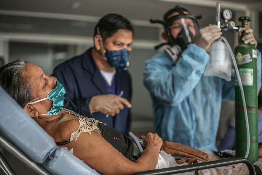 Um médico observa enquanto uma enfermeira verifica o fluxo de oxigênio de uma mu