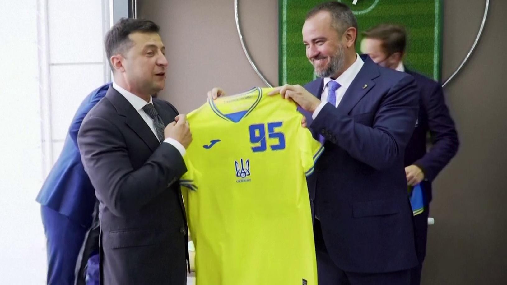 Presidente da Ucrânia, Volodymyr Zelensky, mostra a camisa da seleção do país