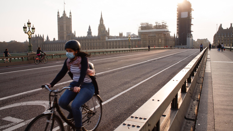 Mulher usa máscara enquanto pedala em frente ao Parlamento inglês, em Londres
