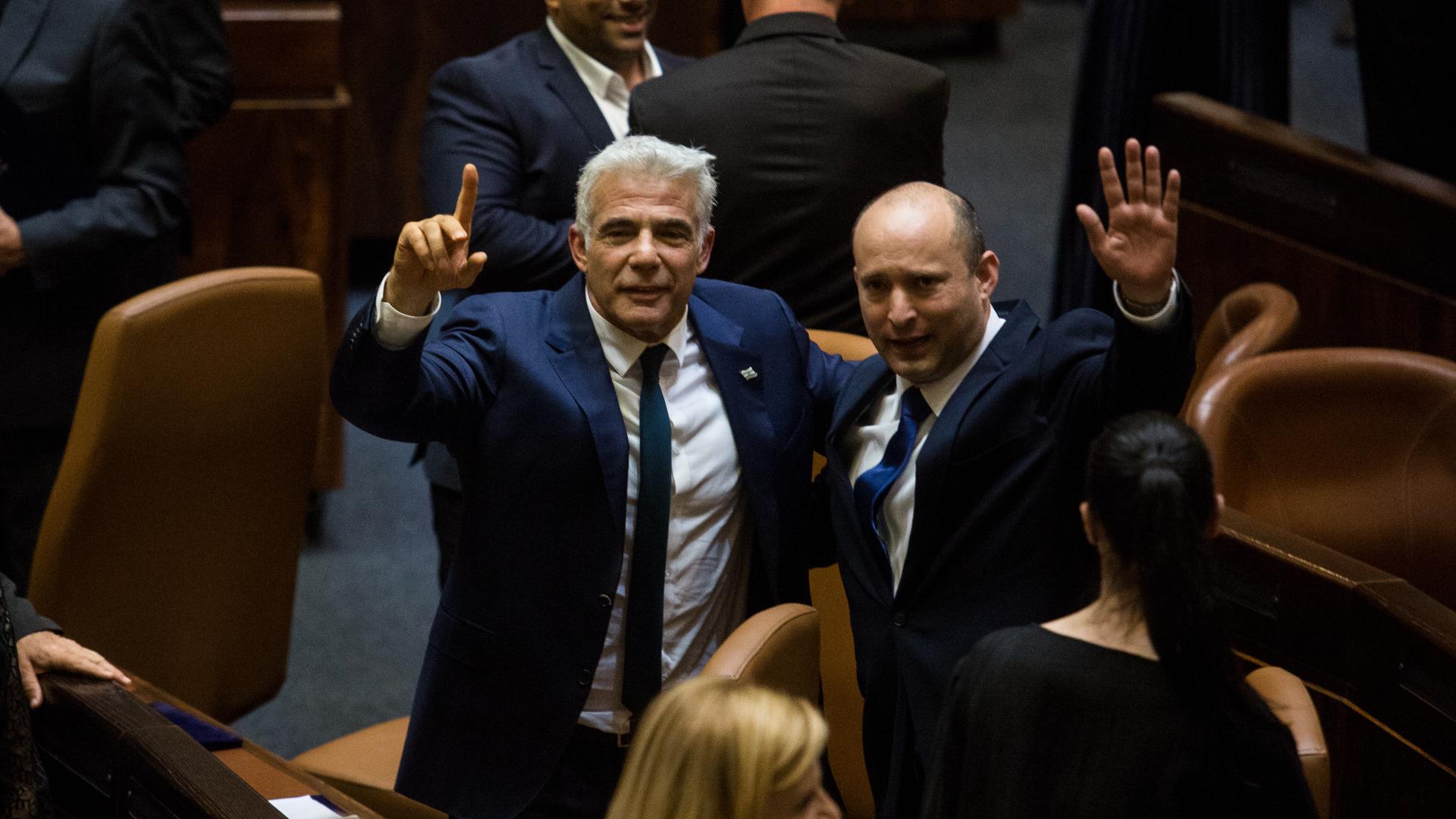 Naftali Bennett acena ao lado de Yair Lapid após votação no parlamento