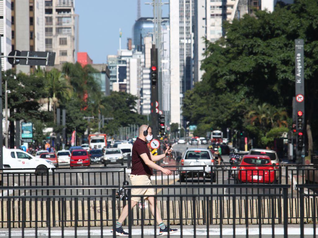 Pedestre utiliza máscara de proteção contra COVID-19 na avenida Paulista.