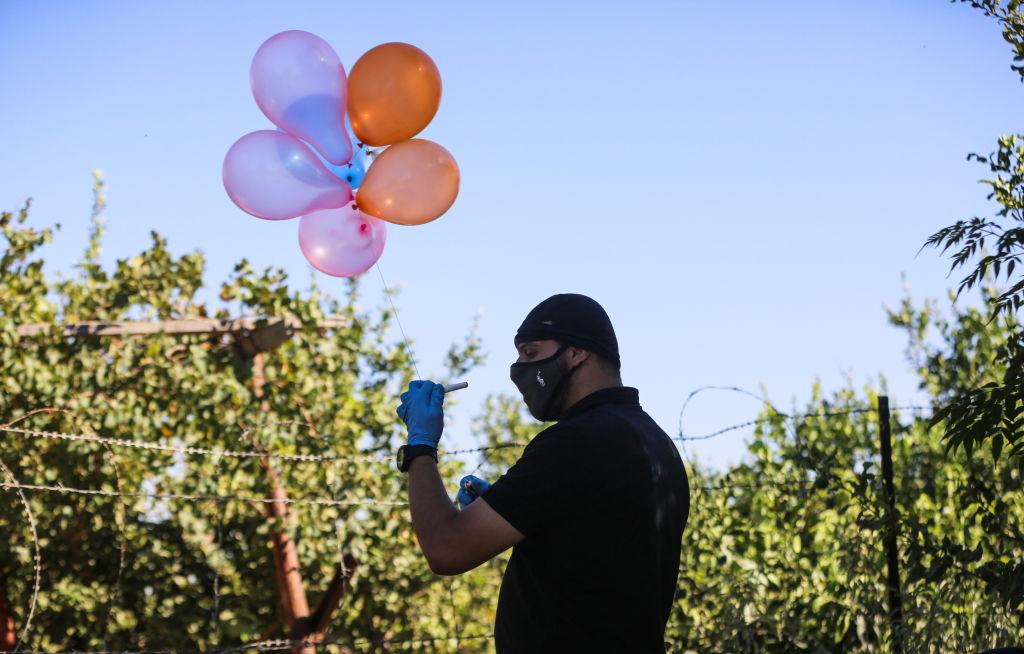 Homem palestino segura balão preso a explosivo